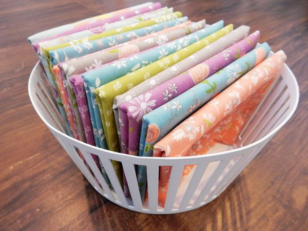 Saturday Seven 125 featured by Top US Quilt Blog, A Quilting Life: image of fabrics in basket